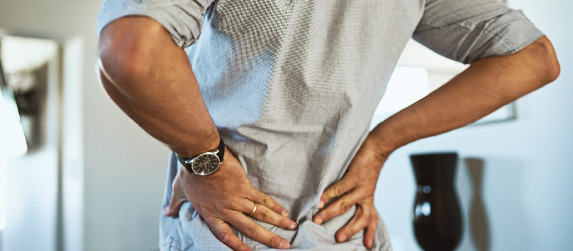Rearview shot of an unrecognizable man holding his back in discomfort due to pain inside at home